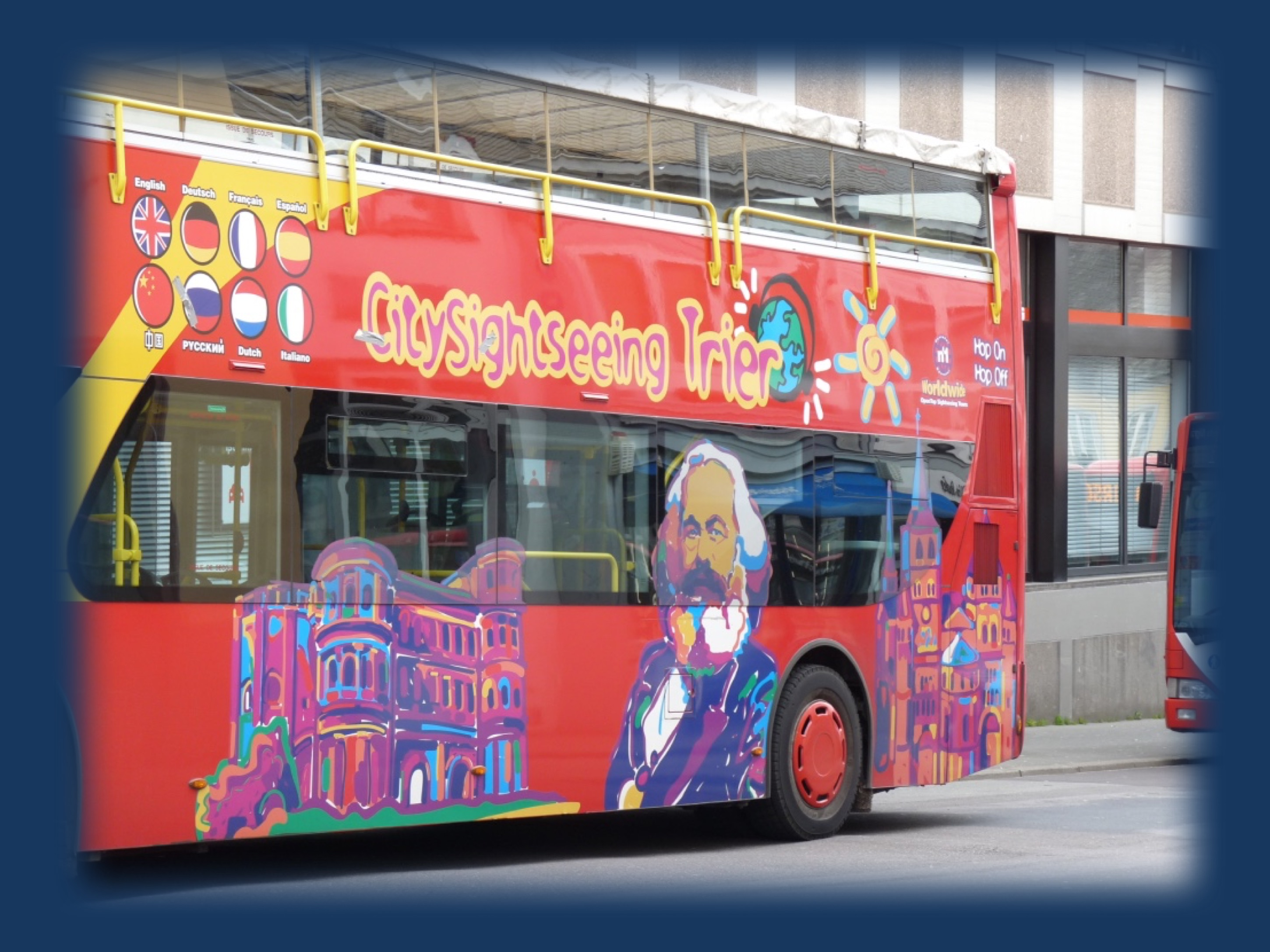 Figure 1. A tourist bus in Trier, Germany featuring Porta Nigra, Karl Marx, and the Trier cathedral.